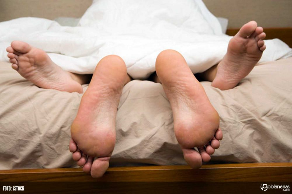 View-of-feet-of-couple-having-sex-in-bed